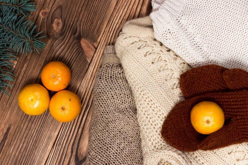 Kerstmis en Nieuwjaar gehaakt Mandarins, bruine handschoenen op de achtergrond van kleurrijke, warme sweaters stock fotografie
