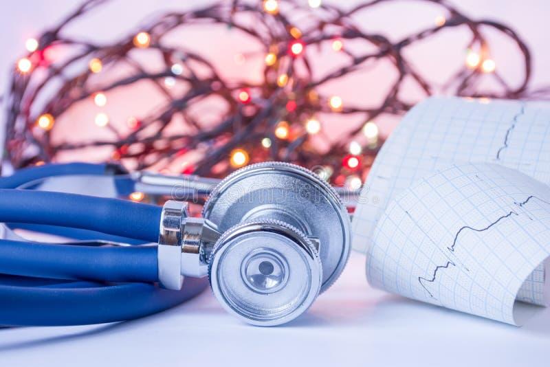 Kerstmis en Nieuwjaar in geneeskunde, algemene praktijk of cardiologie Medische stethoscoop en ECG-band met impulsspoor in foregr royalty-vrije stock afbeeldingen