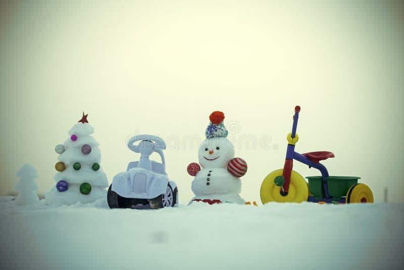 Kerstmis en Nieuwjaar Sneeuwman en sneeuwkerstmisboom op blauwe hemel stock foto's