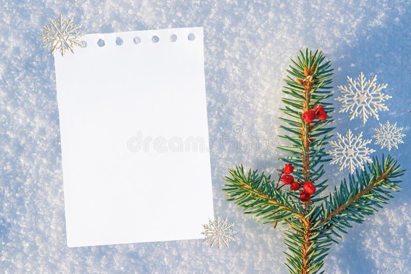 Kerstmis en Nieuwjaarachtergrond leeg wit blad van document voor tekst, groeten op natuurlijke sneeuw met een blauwe tint royalty-vrije stock afbeelding