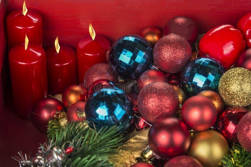 Kerstmis en Nieuwjaardecoratieballen en candels op rode achtergrond stock foto