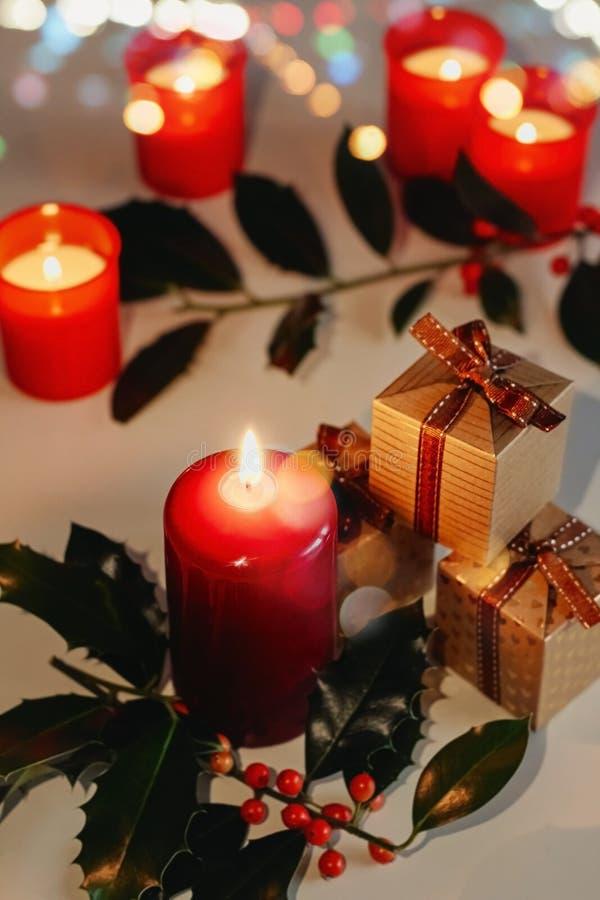 Kerstmis en Nieuwjaarsamenstelling Lit-kaarsen, huidige dozen en tak van hulst stock afbeeldingen