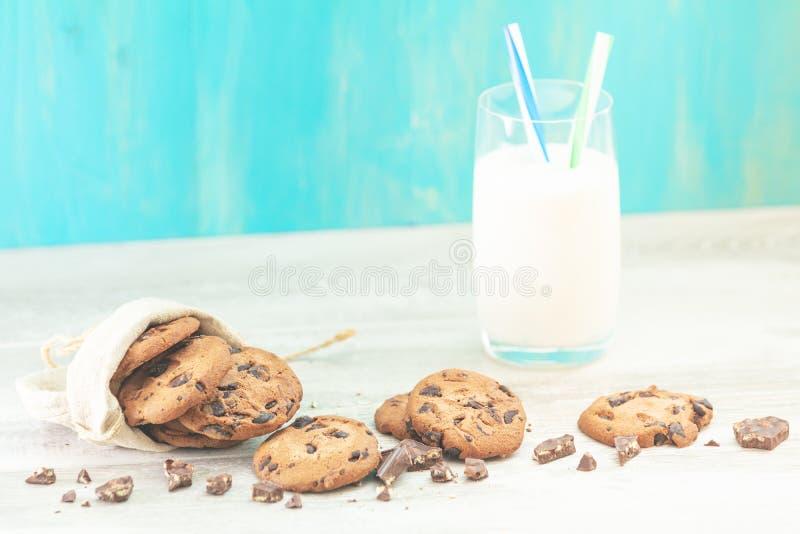 Kerstmis en Nieuwjaarsamenstelling met heerlijk chocoladekoekjes en glas melk op lichte lijst en blauwe achtergrond stock afbeeldingen