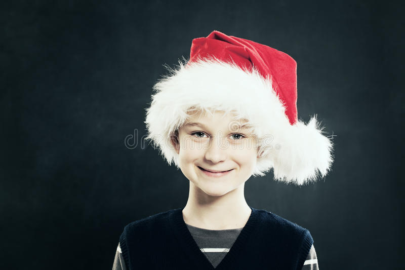 Kerstmis Glimlachend kind in santahoed stock afbeeldingen