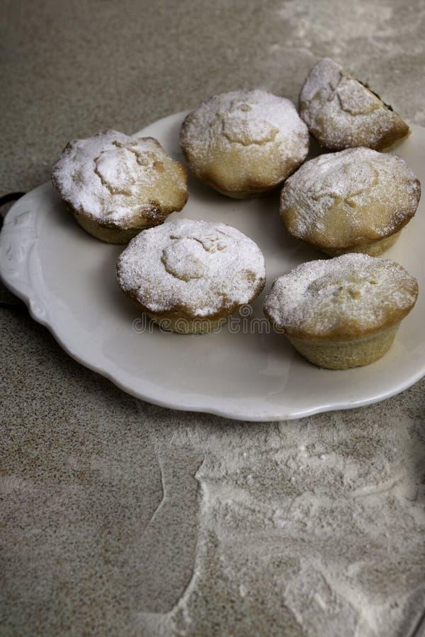Kerstmis hakt pastei fijn door suikerglazuursuiker die wordt bestrooid stock afbeelding