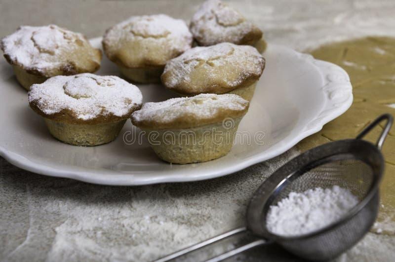 Kerstmis hakt pastei met de zeef van suikerglazuursuiker fijn stock afbeeldingen