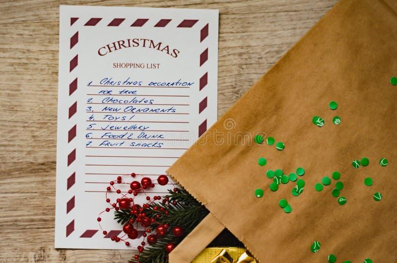 Kerstmis het winkelen lijst met nette tak, het winkelen zak, gift in gouden pakket, ornamenten en groene confettien royalty-vrije stock afbeeldingen
