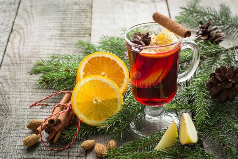Kerstmis hete overwogen wijn met kaneel, sinaasappel en Kerstmisboom aan boord De drank van de de wintertraditie stock afbeeldingen