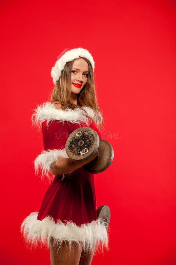 Kerstmis, Kerstmis, de winter, gelukconcept - Bodybuilding Sterke geschikte vrouw die met domoren in santahelper uitoefenen royalty-vrije stock foto