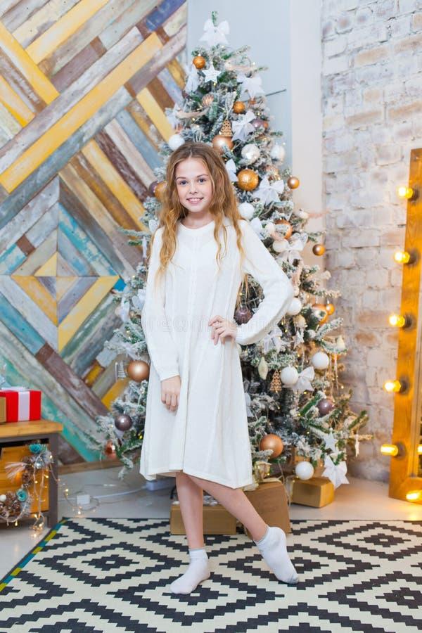 Kerstmis Mooi glimlachend meisje Over de lichtenachtergrond van de Kerstmisboom Gelukkig Nieuwjaar royalty-vrije stock foto