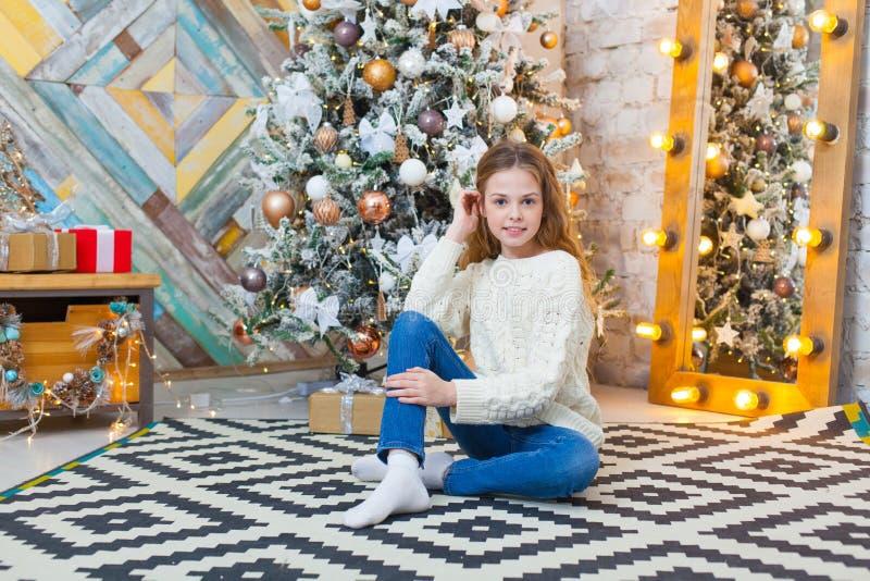 Kerstmis Mooi glimlachend meisje zit over de lichtenachtergrond van de Kerstmisboom Gelukkig Nieuwjaar stock foto
