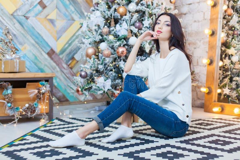 Kerstmis Mooi glimlachend meisje zit over de lichtenachtergrond van de Kerstmisboom Gelukkig Nieuwjaar royalty-vrije stock afbeelding