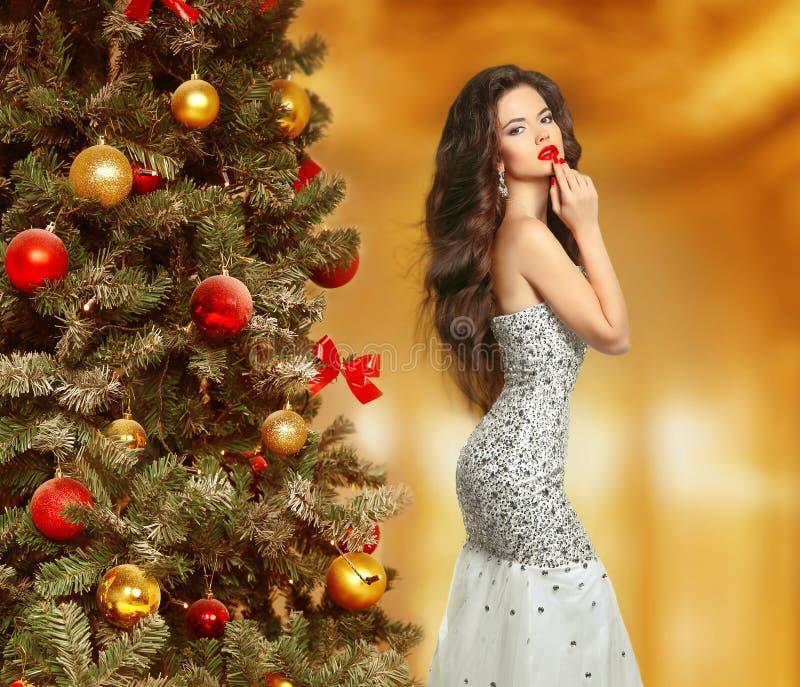 Kerstmis Mooi vrouwenmodel in manierkleding makeup De gezonde Lange Stijl van het Haar Elegante dame in rode toga over de lichten royalty-vrije stock fotografie