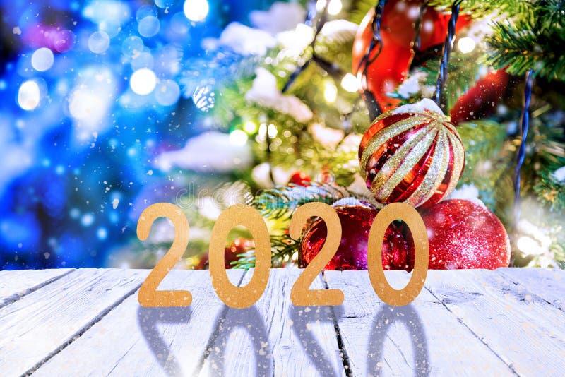 Kerstmis of nieuw jaarkader of model voor uw project 2020 fugures op witte houten tegen de verlichte bomen van feekerstmis stock fotografie