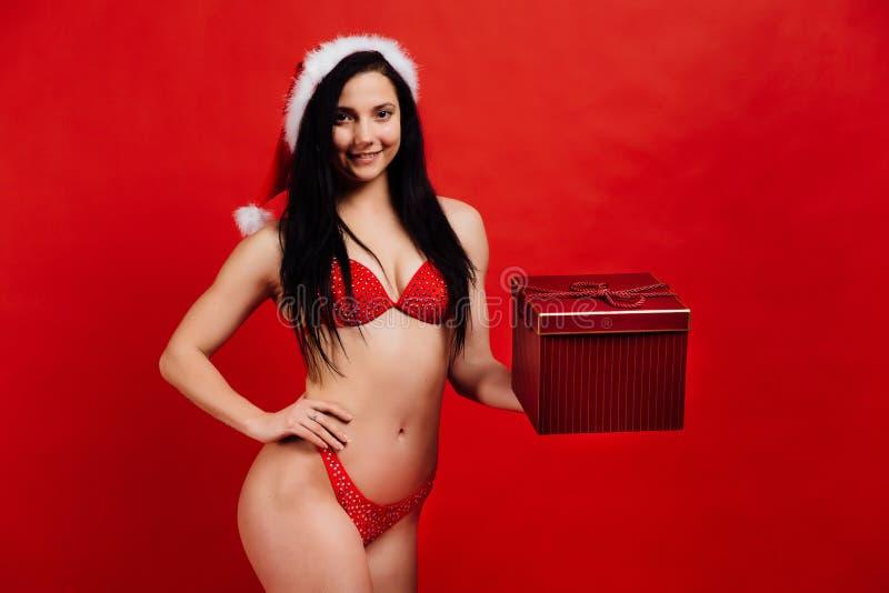 Kerstmis, Nieuwjaar` s vakantie Sexy sporten mooi meisje in bikini de Kerstman met giftdoos stock afbeelding