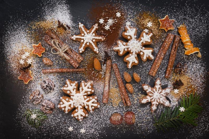 Kerstmis of Nieuwjaarachtergrond van Peperkoekkoekjes, kruiden, noten met suiker en sneeuwvlokken Hoogste mening royalty-vrije stock foto's
