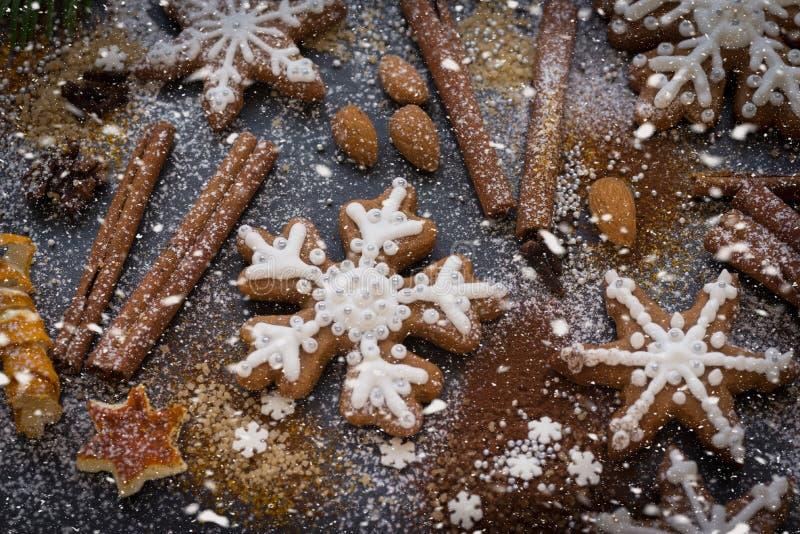 Kerstmis of Nieuwjaarachtergrond van Peperkoekkoekjes, kruiden, noten met suiker en sneeuwvlokken Hoogste mening stock afbeelding