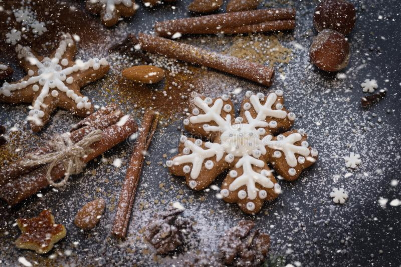 Kerstmis of Nieuwjaarachtergrond van Peperkoekkoekjes, kruiden, noten met suiker en sneeuwvlokken Hoogste mening stock afbeeldingen