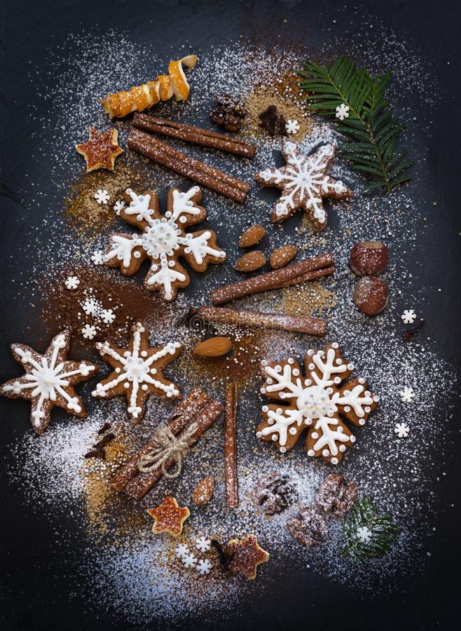Kerstmis of Nieuwjaarachtergrond van Peperkoekkoekjes, kruiden, noten met suiker en sneeuwvlokken Hoogste mening royalty-vrije stock afbeelding