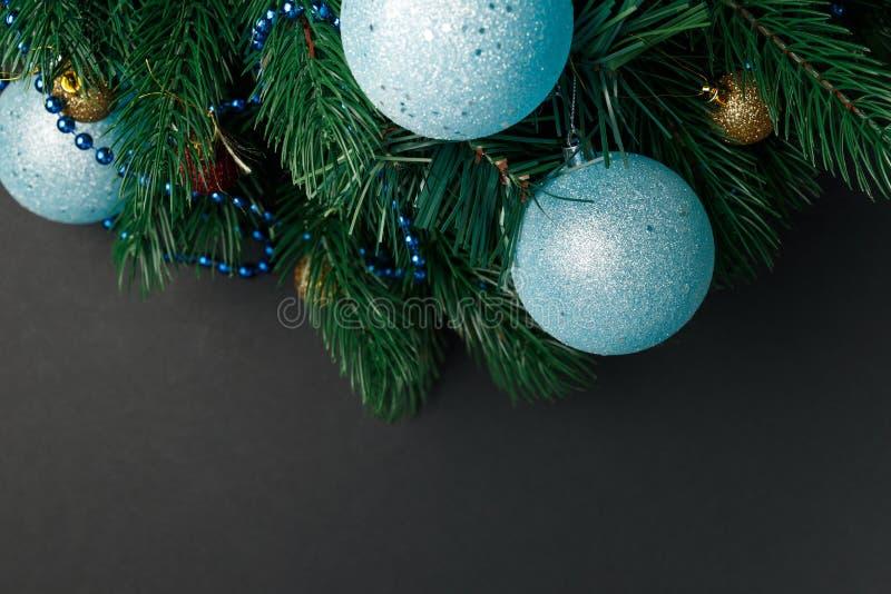 Kerstmis of Nieuwjaardecoratieachtergrond: bont-boom takken, kleurrijke glasballen op zwarte grungeachtergrond Kerstmiscomposi royalty-vrije stock foto's
