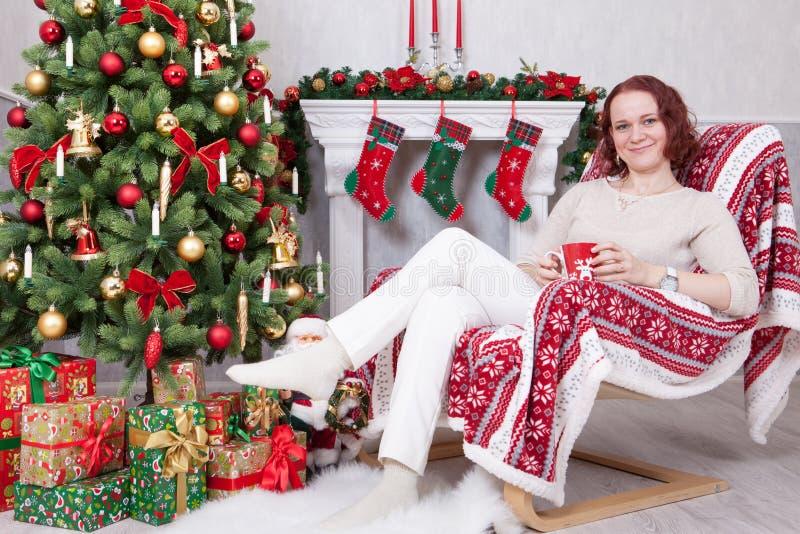 Kerstmis of Nieuwjaarviering De jonge vrouw in een witte gebreide verbindingsdraad houdt een kop en zitting als voorzitter in Ker royalty-vrije stock foto