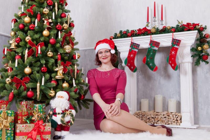 Kerstmis of Nieuwjaarviering Gelukkige vrouw in rode kledingszitting dichtbij Kerstboom met Kerstmisgiften Een open haard met chr royalty-vrije stock afbeelding