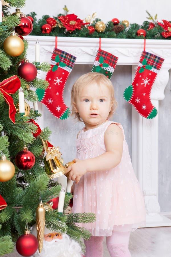 Kerstmis of Nieuwjaarviering Meisje die in leuke roze kleding Kerstboom verfraaien thuis dichtbij de open haard met Christus royalty-vrije stock afbeeldingen