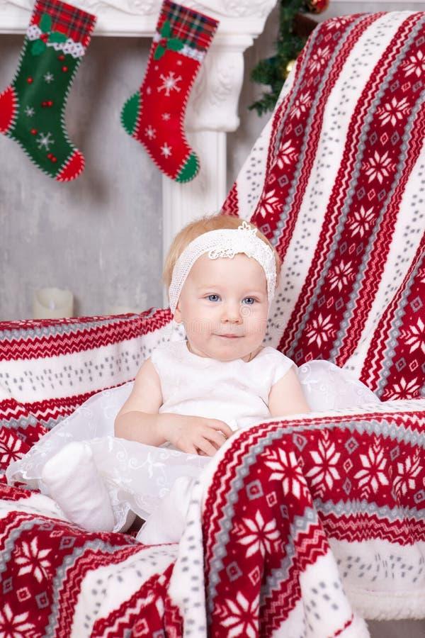 Kerstmis of Nieuwjaarviering Weinig leuk meisje in witte feestelijke kleding zit als voorzitter met plaid met Kerstmisornament ha royalty-vrije stock afbeelding