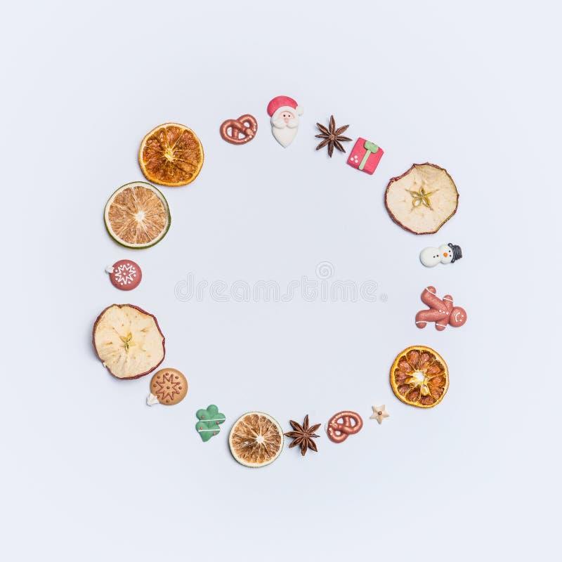 Kerstmis om cirkelbekendheid of kroon maakte met droge vruchten en anijsplantsterren en het decorcijfers van marsepeinkerstmis stock foto's