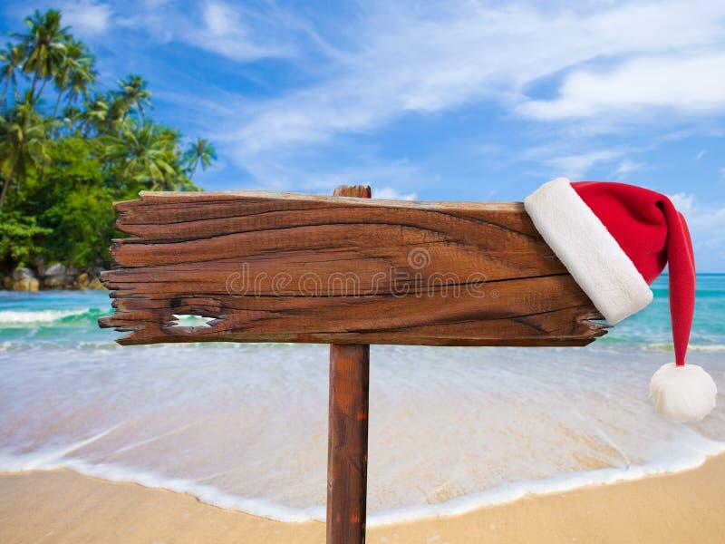 Kerstmis op strandconcept Houten uithangbord met de hoed van de Kerstman royalty-vrije stock foto's