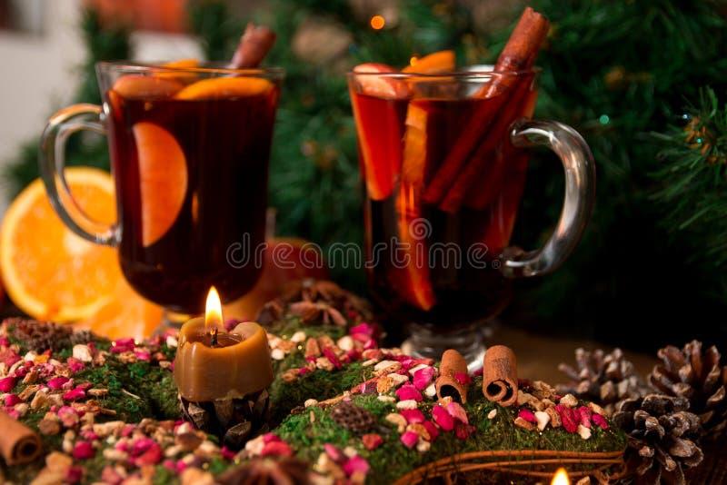 Kerstmis overwogen wijn en ster, kaarsen op houten lijst Kerstmisdecoratie op achtergrond De winter verwarmende drank Twee glazen royalty-vrije stock afbeelding