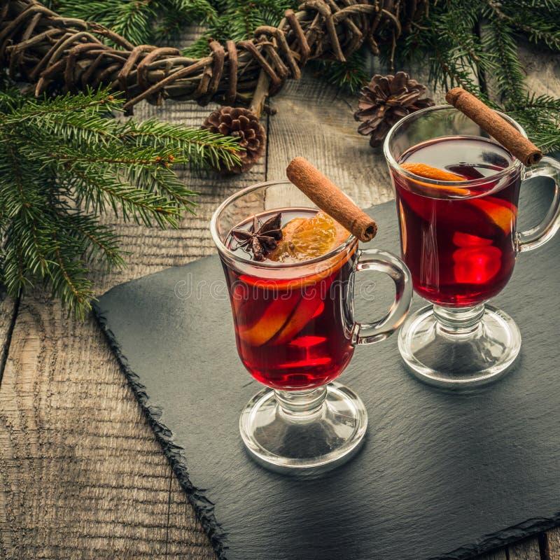 Kerstmis overwogen wijn met kaneel en sinaasappel op houten rustieke raad Traditionele hete drank bij Kersttijd stock afbeelding