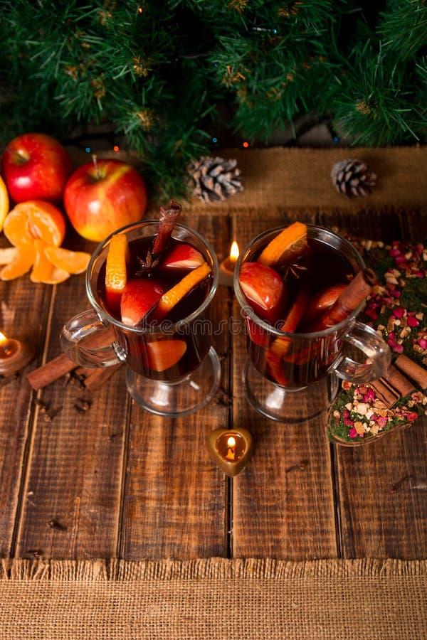 Kerstmis overwogen wijn met vruchten, kaarsen en kruiden op houten lijst Kerstmisdecoratie op achtergrond Twee glazen De winterwa stock foto