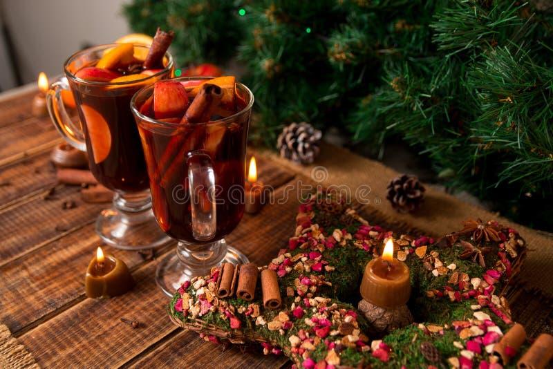 Kerstmis overwogen wijnster, kaarsen op houten lijst Kerstmisdecoratie op achtergrond Twee glazen De winter verwarmende drank stock afbeelding