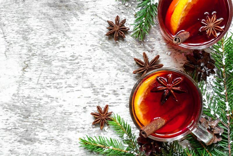 Kerstmis overwoog wijn met kaneel, anijsplant en sparrentakken op witte houten achtergrond stock foto
