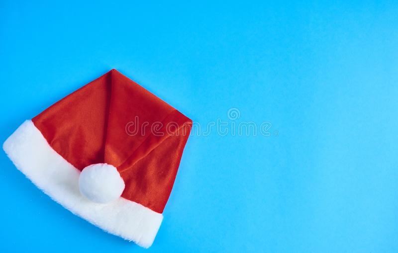 Kerstmis rode die hoed op blauwe achtergrond wordt geïsoleerd Ruimte voor tekst D stock fotografie