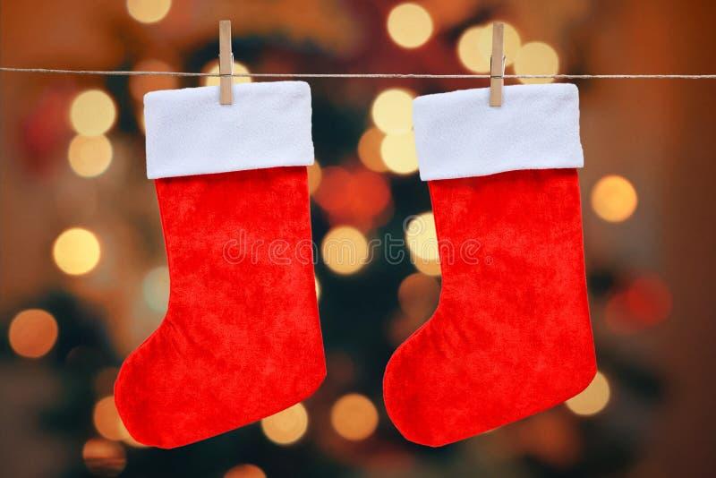 Kerstmis rode die sokken met pinnen op een kabel worden vastgehaakt stock fotografie