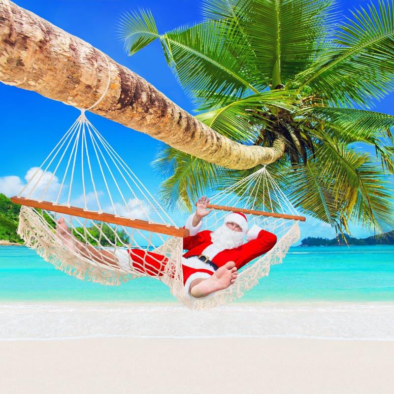Kerstmis Santa Claus ontspant in hangmat bij het tropische strand van het palm zandige oceaaneiland stock foto's