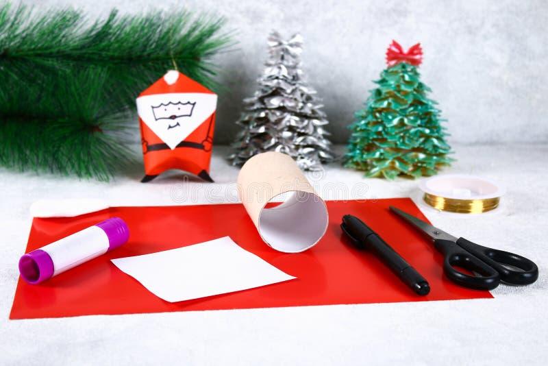Kerstmis Santa Claus van toiletpapierhub, gekleurd document, teller, lijm, vislijn en katoenen stootkussen wordt gemaakt dat DIY- royalty-vrije stock foto