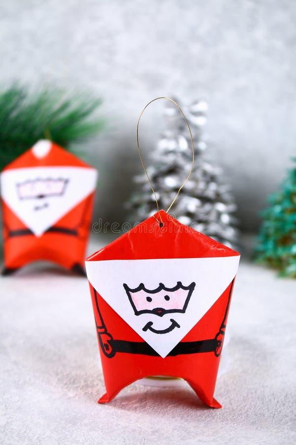 Kerstmis Santa Claus van toiletpapierhub, gekleurd document, teller, lijm, vislijn en katoenen stootkussen wordt gemaakt dat DIY- royalty-vrije stock afbeeldingen