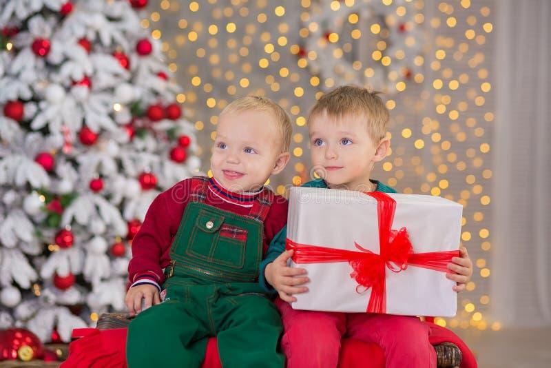 Kerstmis schieten twee kinderenjongens die in studio stellen dicht bij nieuwe jaarboom die fluweel groene en rode kleren dragen stock fotografie