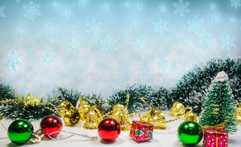 Kerstmis siert achtergrondwhit sneeuwvlokken in blauwe, groene, rode en gouden klokken royalty-vrije stock fotografie