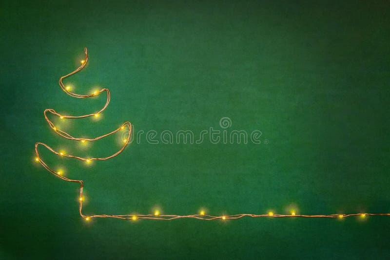 Kerstmis steekt slinger aan als Kerstmisboom wordt geschikt over groene achtergrond die Vlak leg, kopieer ruimte stock foto