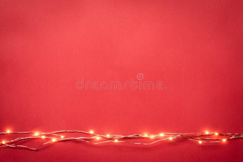 Kerstmis steekt slingergrens over rode achtergrond aan Vlak leg, kopieer ruimte royalty-vrije stock afbeeldingen