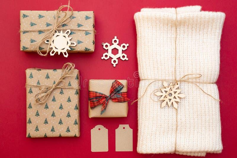 Kerstmis stelt op rode achtergrond voor Kraftpapier-document giftvakjes, gebreide die sjaal in streng, decoratieve sneeuwvlokken  royalty-vrije stock afbeeldingen