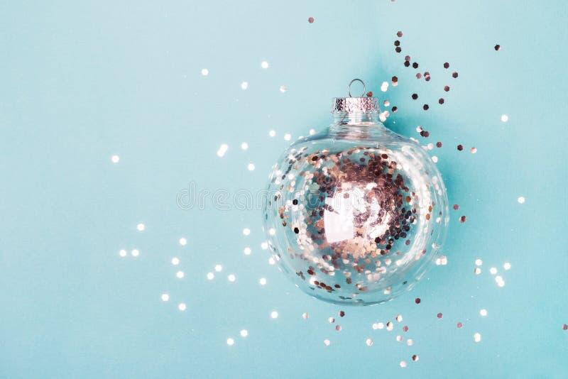 Kerstmis transparante bal met zilveren confettien op blauwe achtergrond Kerstmistak en klokken royalty-vrije stock fotografie