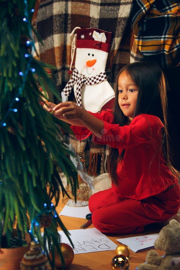 Kerstmis, vakantie en kinderjarenconcept - gelukkig meisje die in rode kleren natuurlijke spar verfraaien stock afbeeldingen