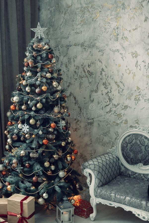 Kerstmis verfraaide spar in studio met stoel stock afbeelding
