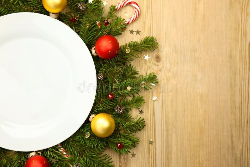 Kerstmis witte plaat met spar op houten achtergrond stock foto's