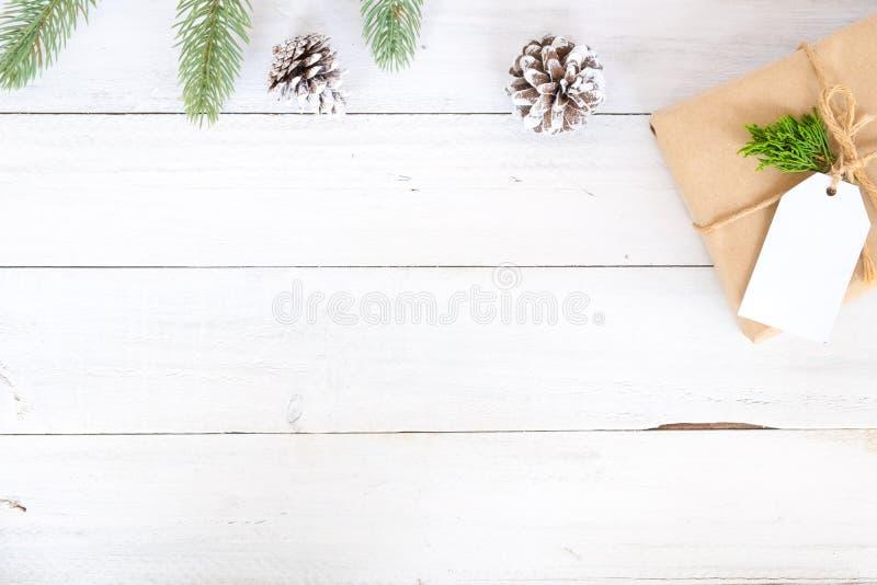 Kerstmisachtergrond met met de hand gemaakte huidige giftdozen en rustieke decoratie op witte houten raad stock fotografie